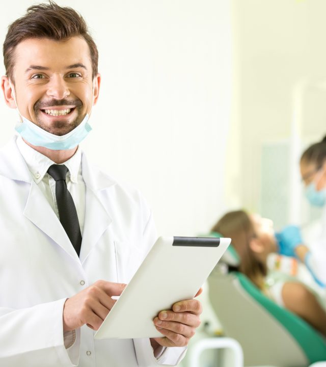 Smiling dentist with a tablet in hands. Another dentist  and patient on background.